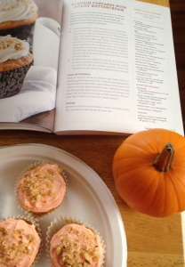 Cookbook and 3 cupcakes arranged artfully with small pumpkin