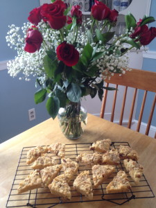 Bouquet of roses in vase with rack of cooling scones in front