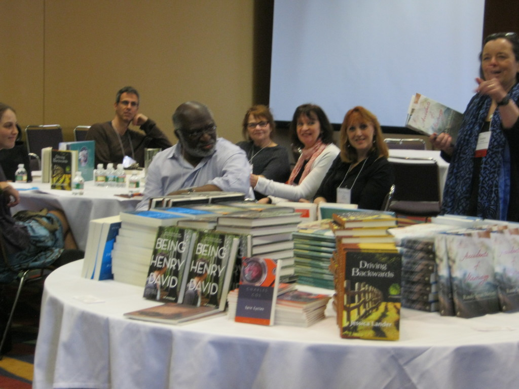 shot of room with books in foreground, authors in background